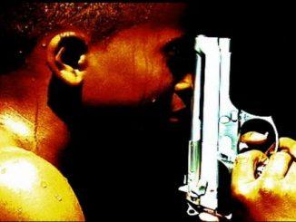 Boy Holding a Gun Bullets over Brownsville
